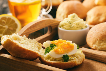 Home breakfast - homemade bread rolls, cup of tea, boiled eggs and garlic herb butter.
