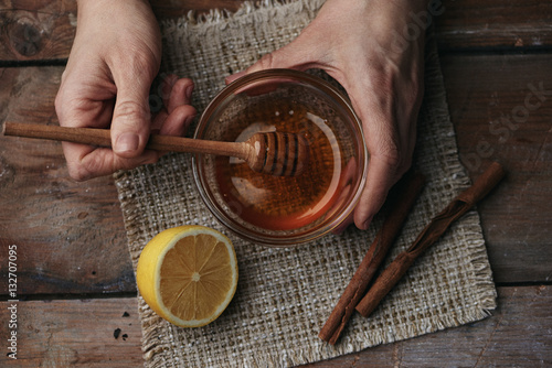 Poster Close-up of female hands holding honey spoon on wooden table with lemon and cinnamon