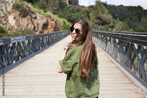 Poster Smiling woman with windy hair in sunglasses on bridge.