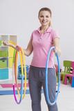Woman holding three hula hoops