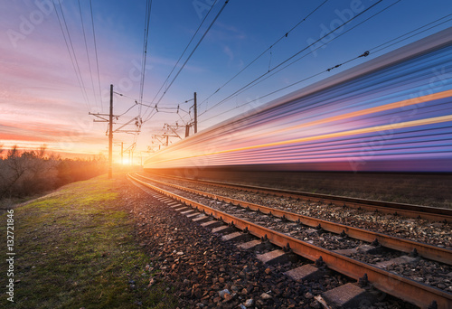 Wysoki prędkość pociąg pasażerski w ruchu na linii kolejowej przy zmierzchem. Zatarcie pociągu podmiejskiego. Stacja kolejowa przeciw pogodnemu niebu. Podróże koleją, turystyka kolejowa. Wiejski krajobraz przemysłowy. Pojęcie