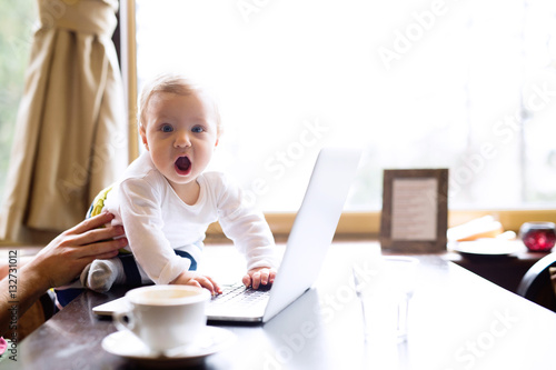 Fotografiet Unrecognizable man in cafe having coffee, holding his son