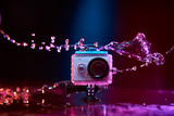 Concept: gear, gadget, action lifestyle, millennial. Vivid colorful shot of action camera in waterproof case splashed with water. Time freeze. - 132733291