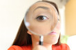 Businesswoman watching you with magnifier glass