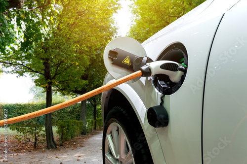 Charging an electric car with the power cable supply plugged in.Flare light effect