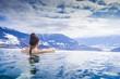 Leinwanddruck Bild - Frau geniesst Bergpanorama im Winter vom Pool aus