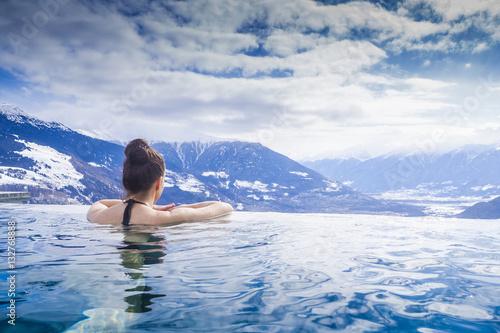 Leinwanddruck Bild Frau geniesst Bergpanorama im Winter vom Pool aus