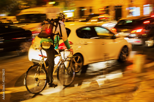 Poster bicycle messenger in city traffic at night