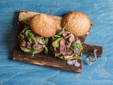 Homemade steak burger on wooden cutting board on a blue background