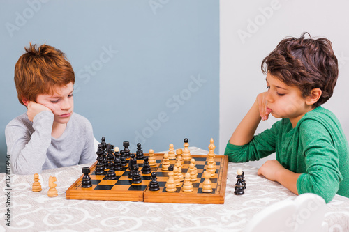 Poster Two brothers are playing chess at home.