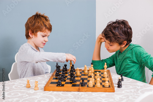 Plakat Two brothers are playing chess at home.