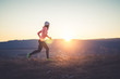 Runner girl on top of the hill in sunset