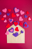 Colored hearts pours out of the envelope. Burgundy background.