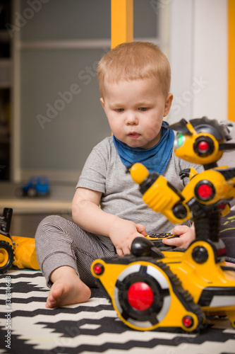 Poster Little toddler boy playing with funny robot toy at home, indoors