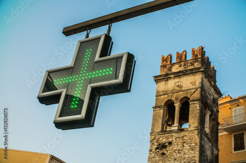 In de dag Apotheek the cross - the sign of the pharmacy hanging on the streets of European cities