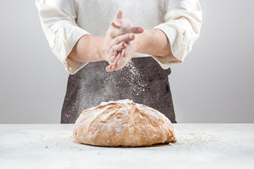 The male hands in flour and rustic organic loaf of bread