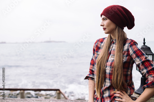 Poster portrait of beautiful young woman in burgundy hat and plaid shirt against the ba