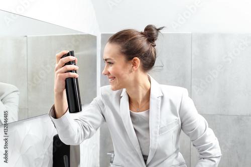 Poster Kapsalon Elegancka pracownica biura. Kobieta biznesu czesze i lakieruje włosy w firmowej toalecie.