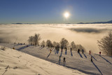 Skiers watching sunrise in the mountains
