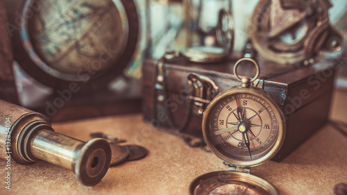 Antique pirate adventure collection including a compass, telescope, treasure wood box and globe models. (vintage style)