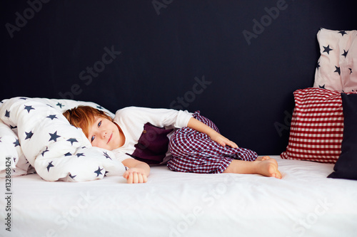 Fotografiet cute kid wearing pajamas, relaxed boy lying in bed