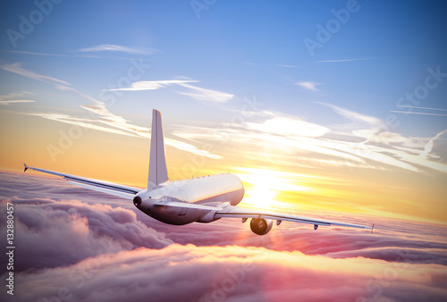 Poster Airplane flying above clouds in dramatic sunset