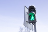 Traffic light with a burning green board on the sky