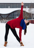 Young athletic woman in a red sweater and a blue scarf performing a slope to the foot against a snowy street outdoors