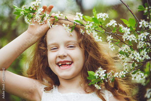 Poster Laughing toothless girl in white dress near blooming cherry tree