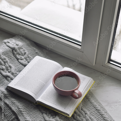 Poster Cozy home still life: cup of hot coffee and opened book with warm plaid on windowsill against snow landscape outside
