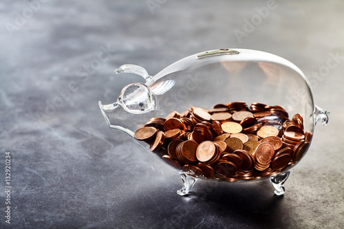 Transparent piggy bank filled with coins