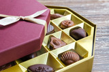 Luxury box of various chocolate candies for Saint Valentines Day. Belgian dark and milk chocolates on wooden table.  Sweets background with copy space.