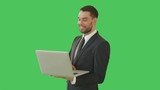 Medium Shot of a Handsome Businessman Holding Laptop Working with a Touchpad. Shot on a Green Screen Background. Shot on RED Cinema Camera 4K (UHD).