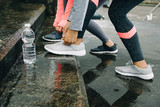 Urban athletes lacing sport footwear for running in the city under the rain. Two women getting ready for outdoor training and fitness exercising on cold winter weather.