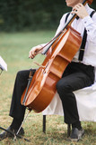 Young man playing cello outside.