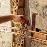 Fontanero colocando una válvula de derivación en las tuberías de cobre