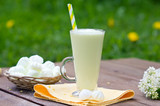 milkshake in a glass beaker with a straw in the open air