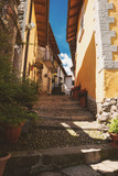 Narrow town street at daytime. Green plants and stone stairs. Explore old district of Stresa.
