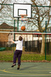 Child playing basketball in a local park