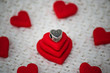 Luxury, trendy jewelry. Delicate and feminine silver charm a small heart. Best gift for Valentines Day and Mothers day. Red heart backgraund.