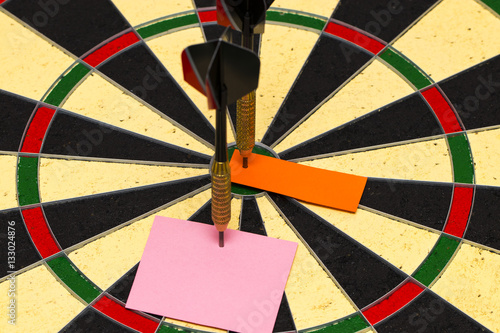 Darts with dart which was pinned a sheet of paper for labels Poster
