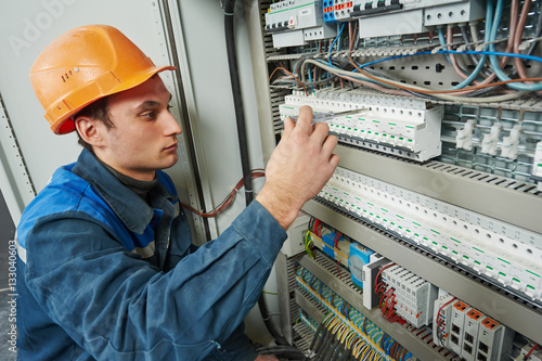 Poster electrician works with electric meter tester in fuse box