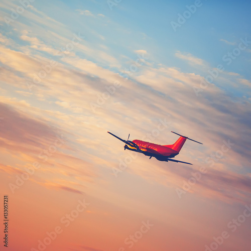 Poster Airplane taking off at the sunset sky