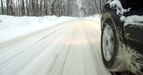 Color footage of a car driving on a snowy road, with close up on the wheel.