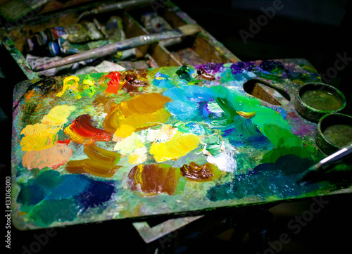 Brushes and artist's palette closeup. Composition on a dark background. Selective focus © yusev