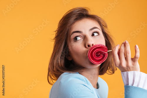 Funny amusing young woman covered her lips with lollipop Poster