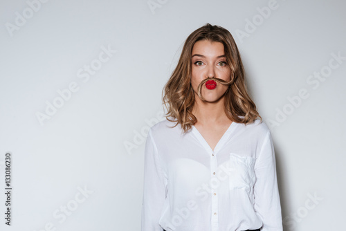 Woman making mustache with a long strand of her hair Plakat