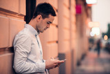 Fototapety Handsome young man text messaging on a city street