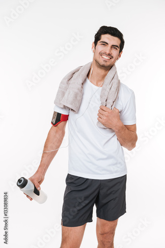 Poster Smilling young sports man drinking water and resting with earphones