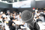 Microphone with blurred photo of conference hall or seminar room